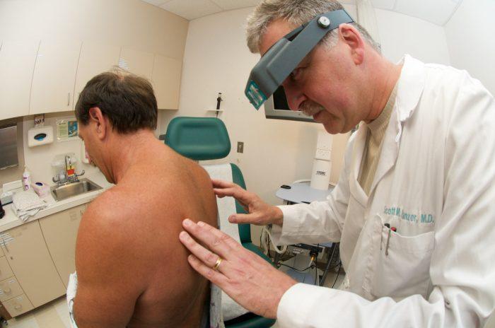 дерматолог проводит визуальное обследование